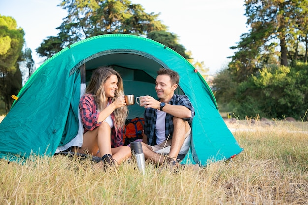 Young couple sitting in tent, talking and drinking tea from thermos. happy hikers relaxing on lawn, camping, smiling and enjoying nature on weekends. tourism, adventure and summer vacation concept
