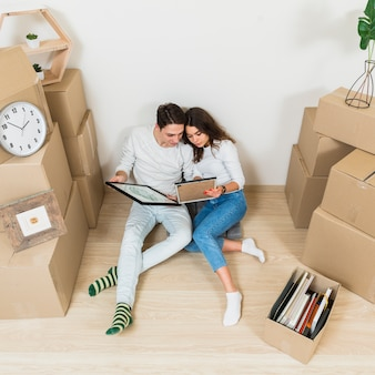 Young couple sitting together looking at picture frame in their new apartment