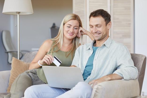 クレジットカードでオンラインで支払うためにラップトップを使用してソファに一緒に座っている若いカップル