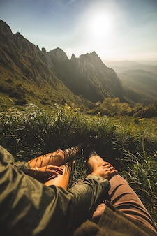 Young couple sitting on top of the mountain and enjoying the view during sunset