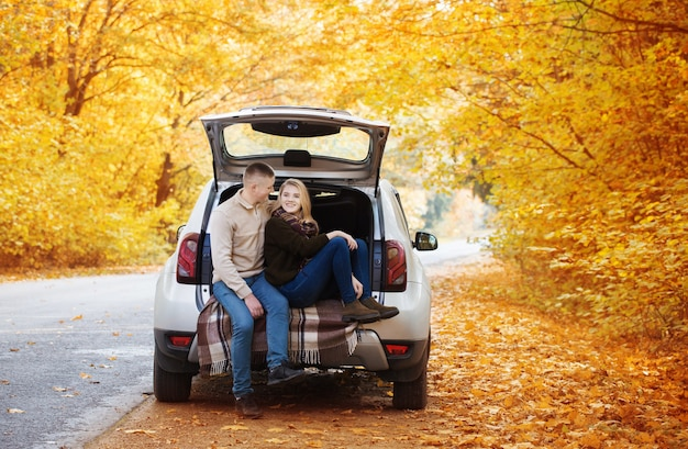 Young couple sitting in the trunk of a car on the road in autumn