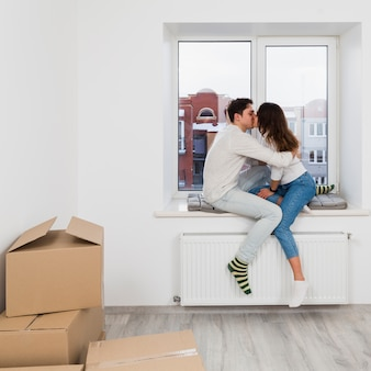 Young couple sitting on window sill kissing each other in their new home
