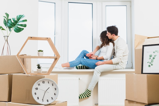Young couple sitting on window sill looking through window with many cardboard boxes
