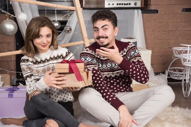 クリスマスと一緒に座っている若いカップルは、お祝いの銀のボールの近くにプレゼントします。