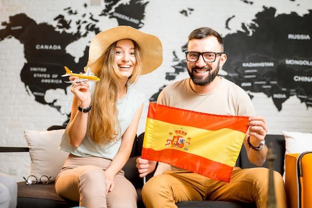 스페인 여행을 준비하는 세계 지도 배경의 여행사 사무실에 스페인 국기를 들고 앉아 있는 젊은 부부