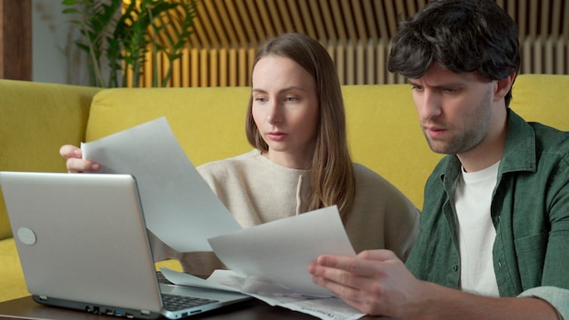 Young couple sitting on yellow sofa at home and managing budget using laptop