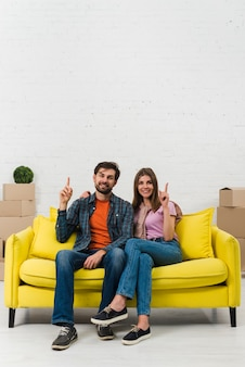 Young couple sitting on yellow sofa pointing their fingers upward and looking to camera