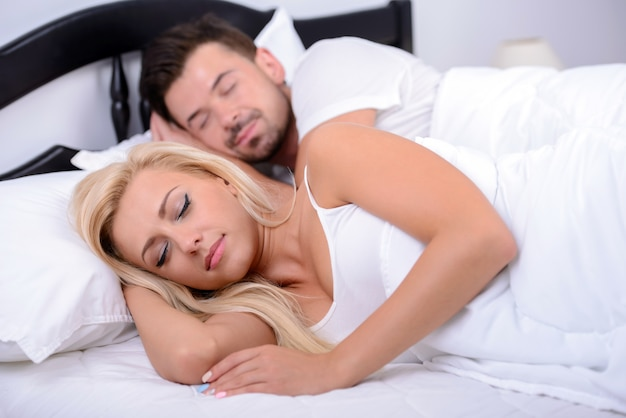 Young couple sleeping in a bed in her bedroom.