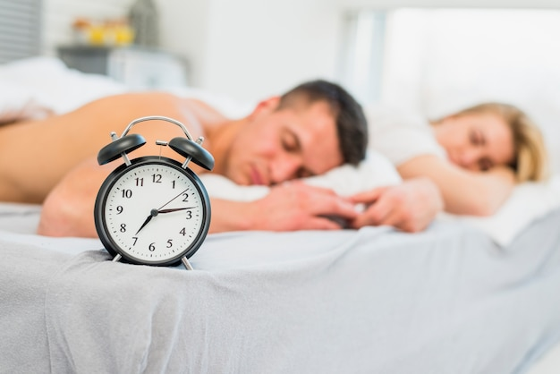 Young couple sleeping on bed near alarm clock