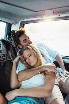 Young couple sleeping in car