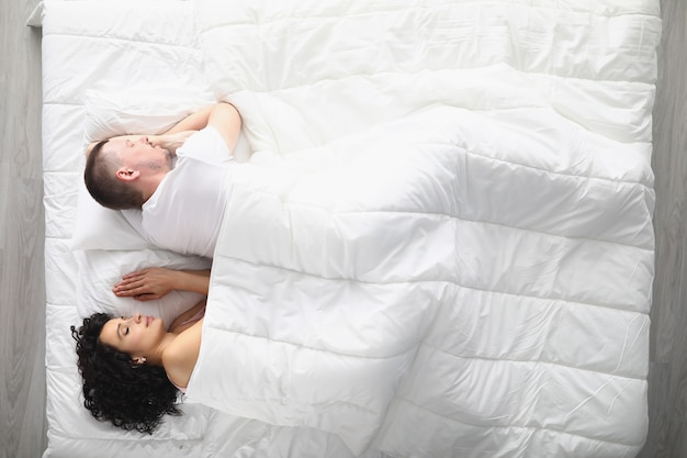 Young couple sleeping peacefully on large comfortable bed