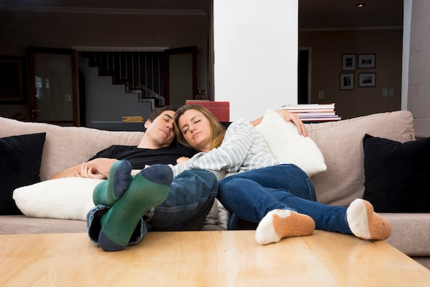 Young couple sleeping together on sofa at home