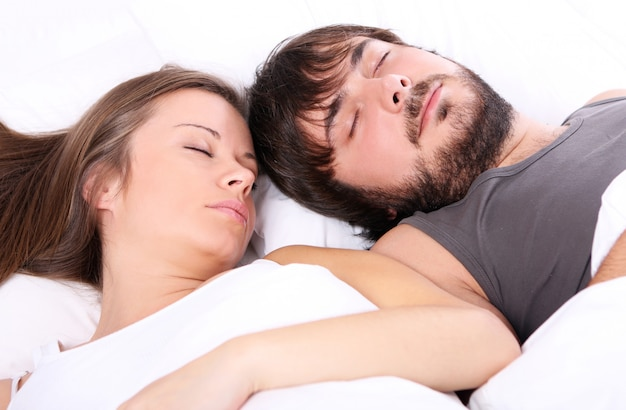 Young couple sleeps in bed