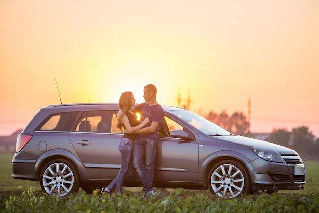 젊은 부부, 긴 머리와 잘 생긴 낚시를 좋아하는 남자를 가진 호리호리한 매력적인 여성은 일몰이나 일출 복사 공간 배경에서 밝은 하늘에 따뜻한 여름 저녁에 은색 차에서 함께 포옹 서 있습니다.