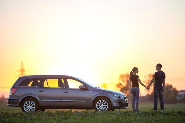 Молодая пара, стройная привлекательная женщина с длинным хвостом и красивый мужчина, стоящий на серебряной машине в зеленом поле на ясном небе на закате или восходе солнца, копируют космический фон.