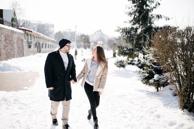 若いカップルは笑顔と冬の公園でキス