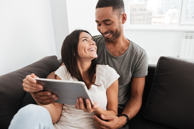 若いカップルは、屋内のソファに座って、タブレットコンピューターを使用しながら一緒に笑顔。お互いを見てください。