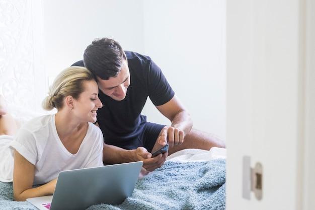 自宅でラップトップで作業しながら笑顔で携帯電話を使用している若いカップル。自宅のベッドで妻と携帯電話を使用してメディアコンテンツを共有している男性。携帯電話でビデオを見ているカップル