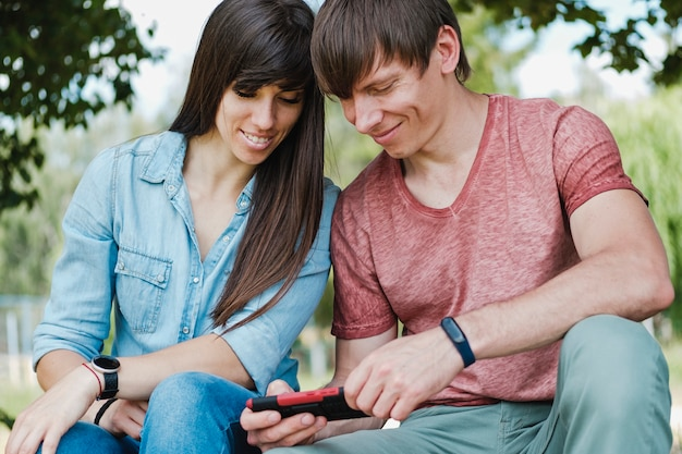 Young couple smiling as they read a phone message