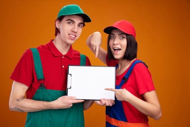 若いカップルの笑顔の男は、建設労働者の制服を着た女の子を興奮させ、キャップの男は、オレンジ色の壁に隔離されたカメラを見て、それを指しているクリップボードの女の子を示しています