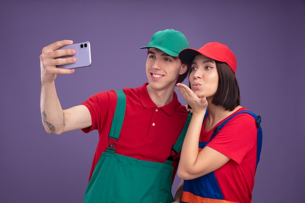 Young couple smiling guy serious girl in construction worker uniform and cap taking selfie together girl sending blow kiss isolated on purple wall