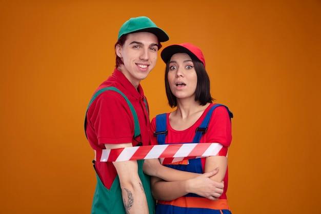 若いカップルの笑顔の男は、建設労働者の制服を着た女の子を驚かせ、腕に手を組んで安全テープの女の子と縛られたキャップ