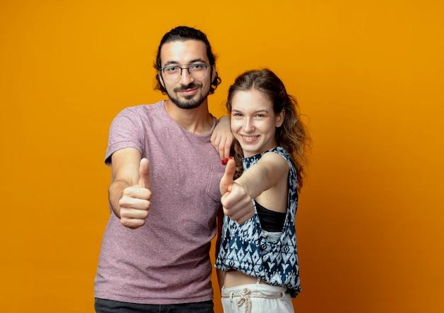 オレンジ色の壁の上に立って親指を見せて幸せで前向きに笑っている若いカップル