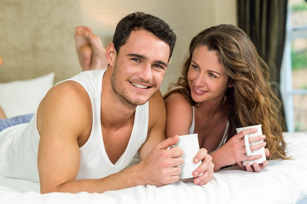 Young couple smiling and having cup of coffee on bed