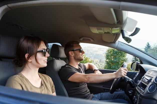 Молодая пара улыбается, сидя в машине, наслаждаясь видом на горы