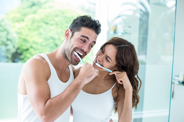 Young couple smiling while brushing teeth