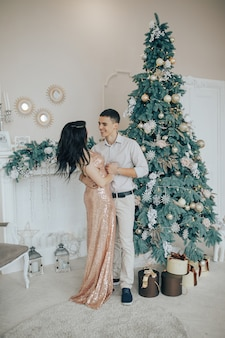 Young couple smiling while celebrating at home near a christmas tree