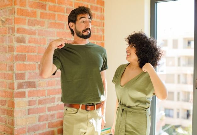 あごに手を当てて幸せで自信に満ちた表情で笑って、不思議に思って横を向いている若いカップル