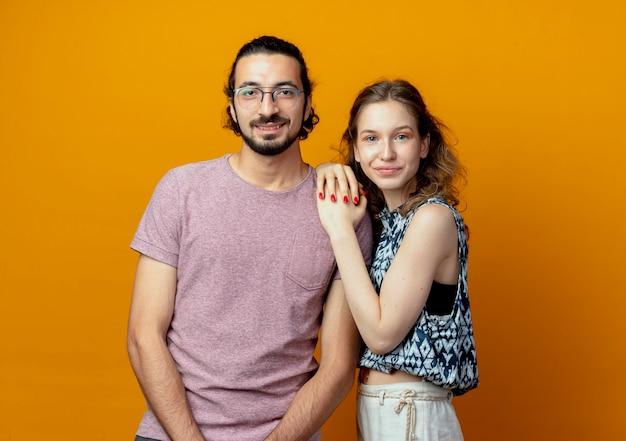Giovane coppia sorridente con facce felici in piedi sopra il muro arancione