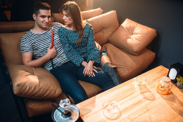Young couple smoking hookah on leather couch