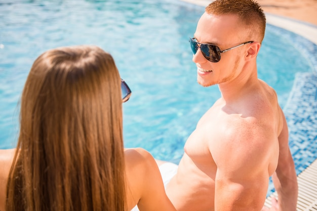 Young couple spend time together in swimming pool.