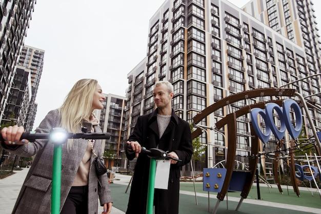 電動スクーターに楽しい時間を費やしている若いカップル。背景にモダンなアパートのブロック。男性と女性が電動スクーターを借りました。ファストトリップのコンセプト。環境にやさしい輸送。大都市のコンセプトの秋。