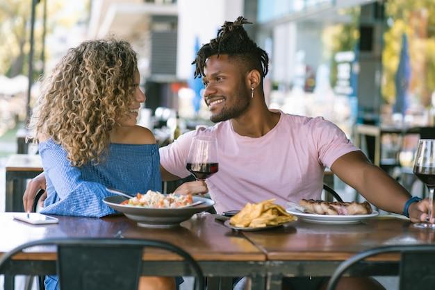 一緒に楽しい時間を過ごし、レストランで昼食をとりながら楽しんでいる若いカップル。
