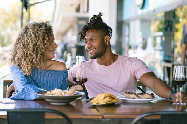 Young couple spending good time together and enjoying while having lunch at a restaurant.