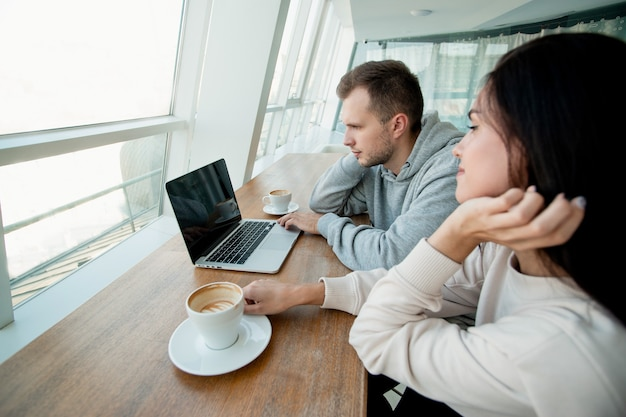 Young couple spending time in cafe and wathcing video on laptop. woman and man drinking coffee and looking photos togehter. cafe on background. woman fixing her hair when man using laptop.