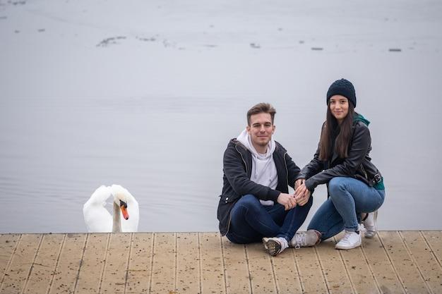 Молодая пара проводит время вместе, и лебедь присоединился в туманный зимний день