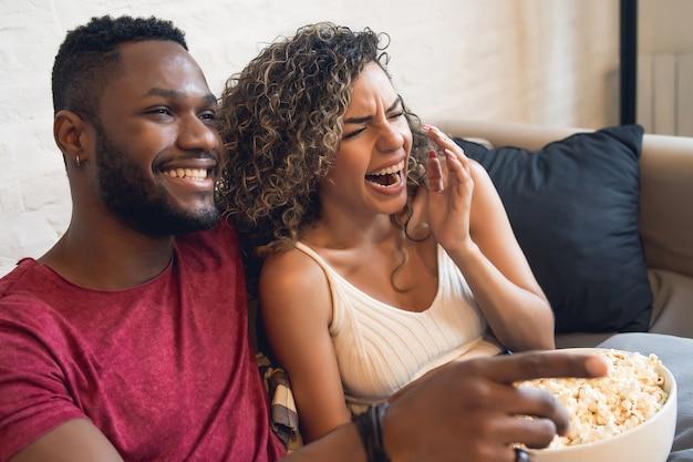 一緒に時間を過ごし、自宅のソファに座ってテレビシリーズや映画を見ている若いカップル。