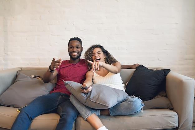 Молодая пара проводит время вместе и смотрит сериал или фильмы, сидя на диване у себя дома.