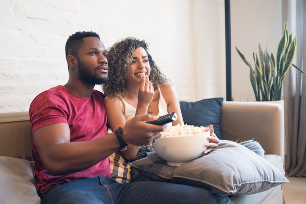 젊은 부부는 함께 시간을 보내고 집에서 소파에 앉아 tv 시리즈나 영화를 봅니다.