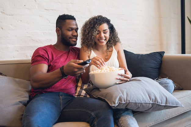 Young couple spending time together and watching tv series or movies while sitting on couch at home.