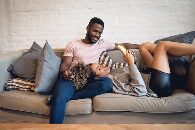 自宅のソファに座って一緒に時間を過ごす若いカップル。新しい通常のライフスタイルのコンセプト。