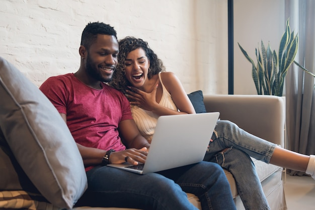 自宅でノートパソコンを使用しながら一緒に時間を過ごす若いカップル。新しい通常のライフスタイルのコンセプト。