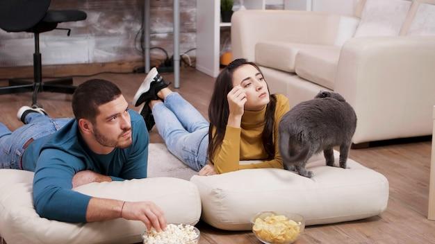 テレビを見ながら猫と過ごす若いカップル。床に座って、チップスとポップコーンを食べるカップル。
