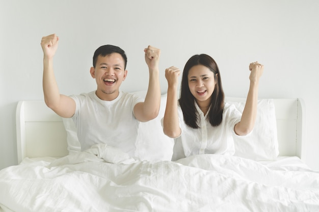 Young couple sport fans cheering team victory while watching football match on tv at home.