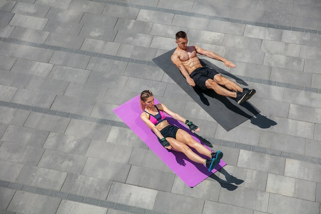 Young couple in sports outfit doing morning workout outdoors.