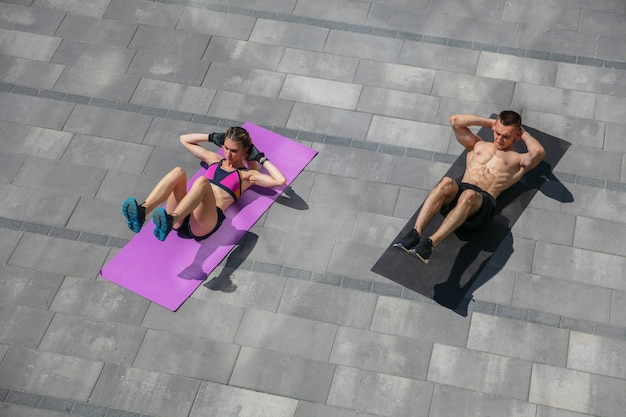 Young couple in sports outfit doing morning workout outdoors
